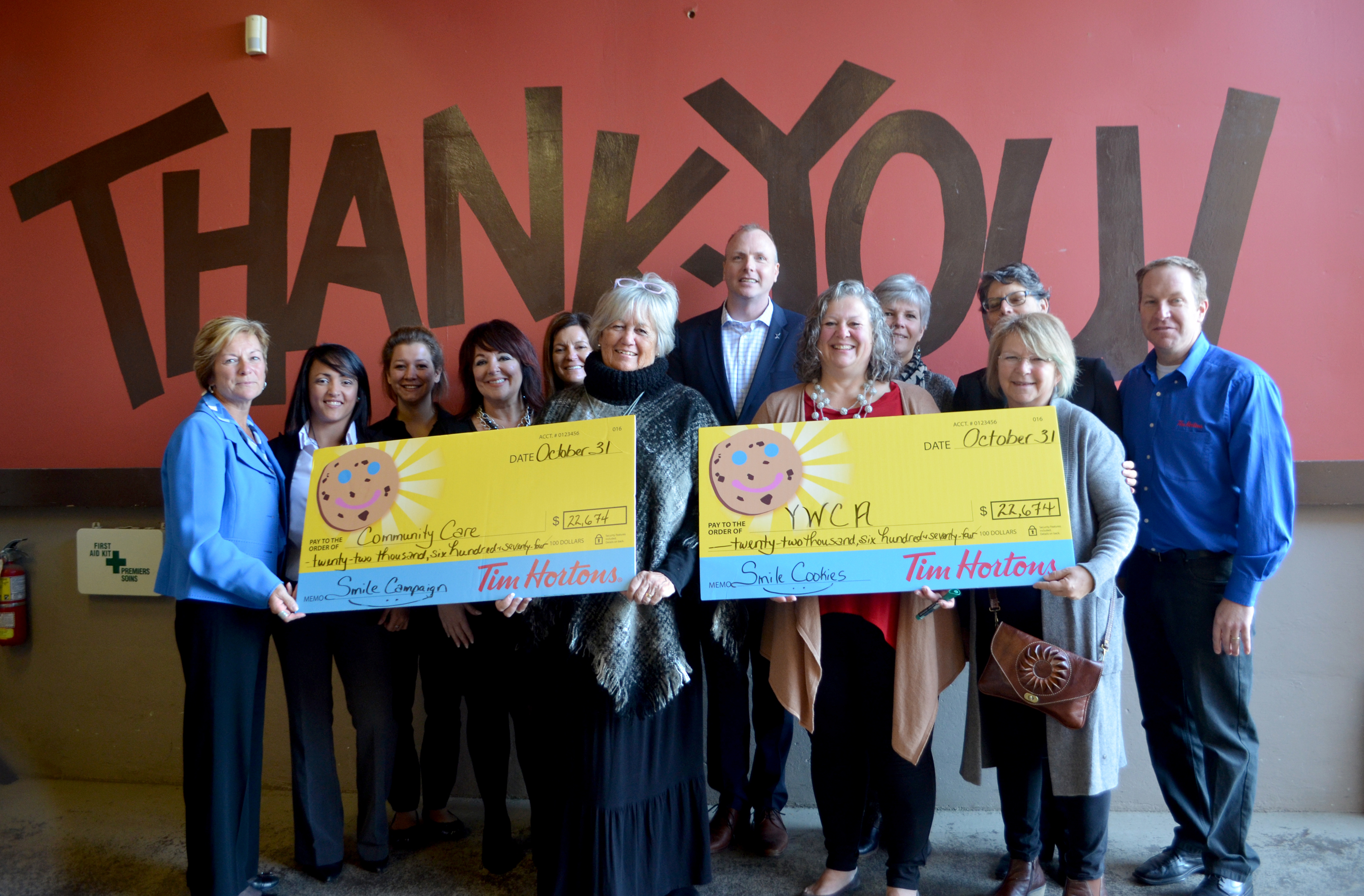 Tim Horton Franchise owners presenting the cheque for the proceeds from the Smile Cookie Campaign. Receiving the cheque are board members from both charities; CEO Betty Lou Souter of Community Care; Executive Director Elisabeth Zimmerman from the YWCA; Laura Byers, Fund Development Officer, Community Care; Nicki Inch, Fund Developer, YWCA.