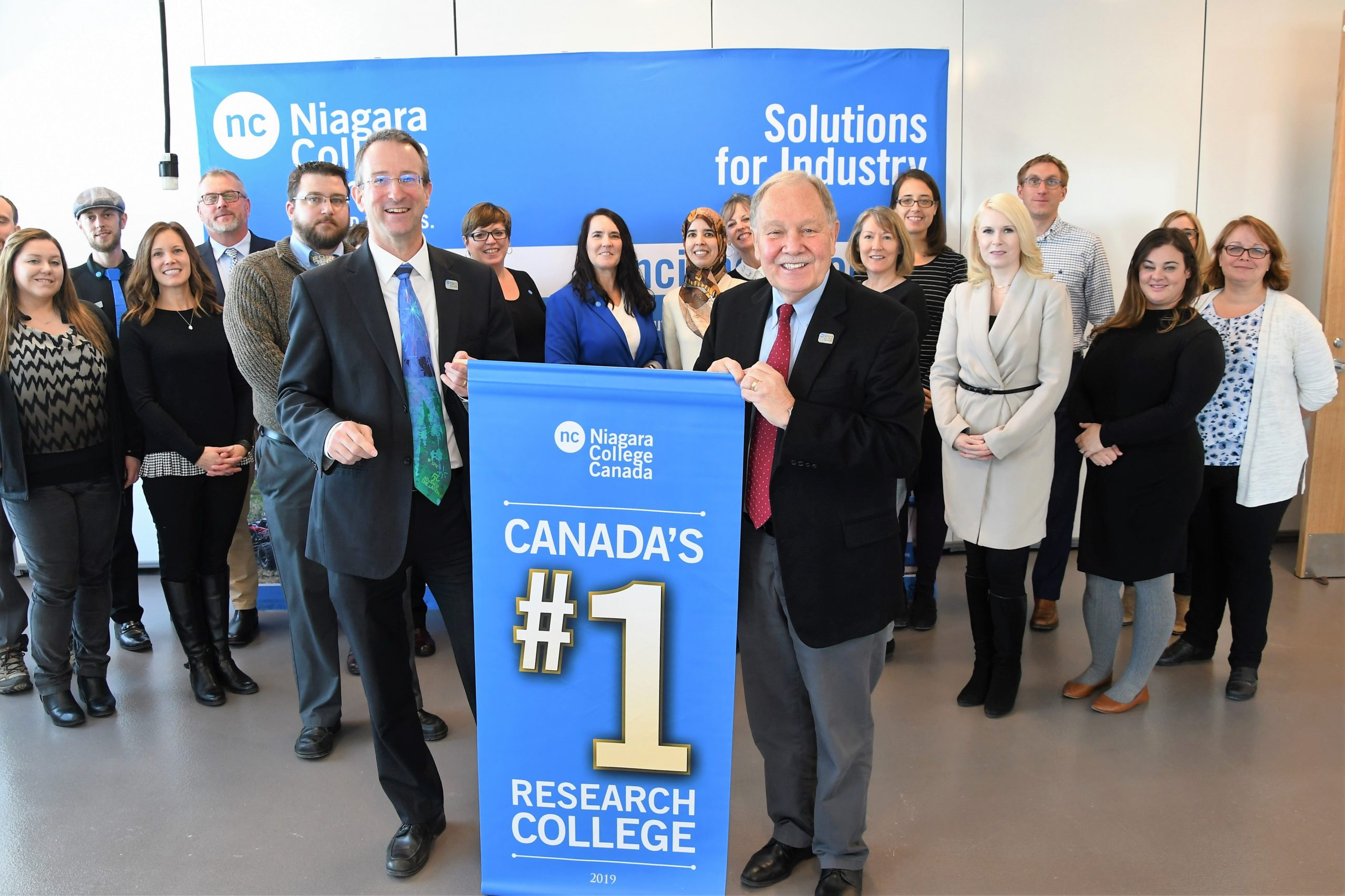 On November 12, Niagara College announces its number one ranking in Research Infosource Inc.'s Top 50 Research Colleges. President Dan Patterson (front right) and VP Research, Innovation & Strategic Initiatives Marc Nantel (front left) hold up a banner announcing the good news as they gather with staff members from NC's Research & Innovation division.