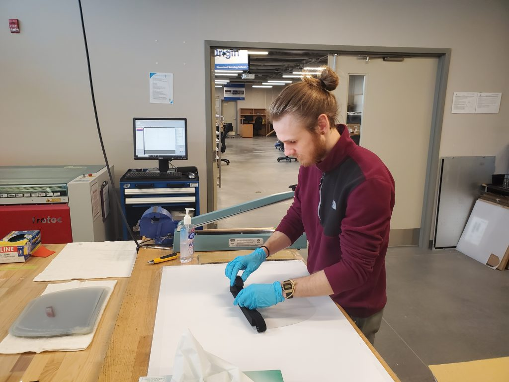Research associate Brock Husak (graduate of NC's Mechanical Engineering Technology program) assembles face shields inside Niagara College's Walker Advanced Manufacturing Innovation Centre to meet the need for critical health supplies.